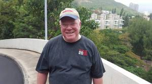 A smiling missioner after an hour-long hike up and down mountains at Stanley