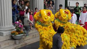 Lion dancers greet people leaving church